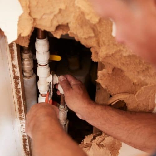Plumber fixing busted pipe inside wall